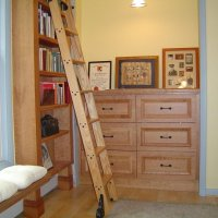 Custom built in home library is traditional style, clear lacquer on cherry wood with custom made solid oak putnam rolling ladder.